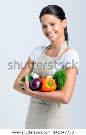 Portrait of young beautiful woman holding raw produce in her arm, peppers, broccoli, dill, mushrooms, aubergine - stock photo