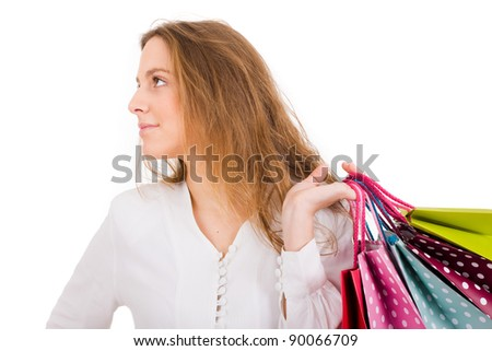 Portrait of young beautiful woman holding shopping bags against white background