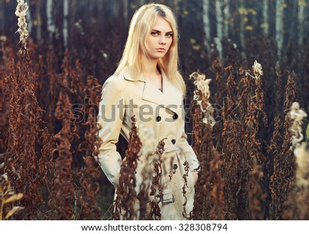 Portrait of young beautiful woman in autumn cloak. Fashion photo. Blonde girl. Perfect make-up - stock photo