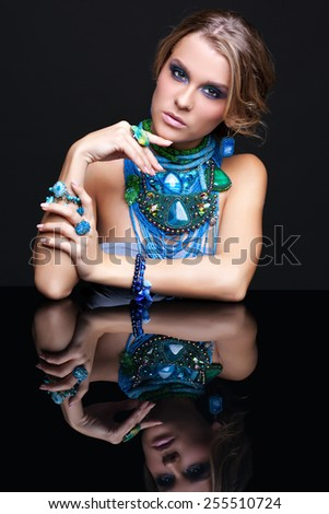 Portrait of young beautiful woman in jewelery at reflecting table on black background - stock photo