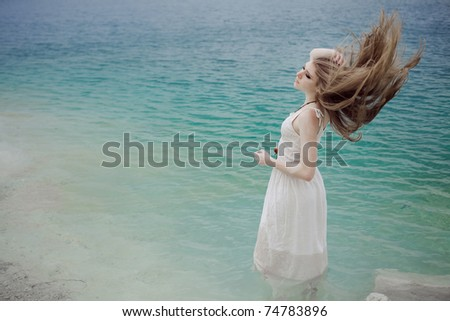 Portrait of young beautiful woman in lake in a white dress with flying hair - stock photo