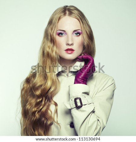 Portrait of young beautiful woman in purple gloves. Fashion photo - stock photo