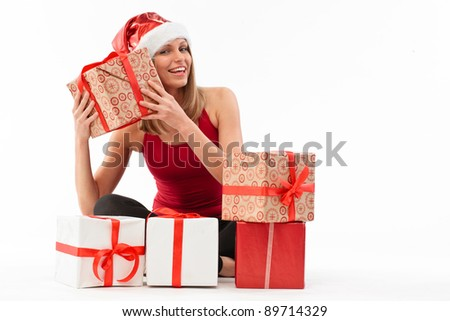 Portrait of young beautiful woman in santa claus hat with many christmas gift boxes. - stock photo