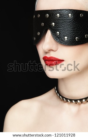Portrait of young beautiful woman in studded blindfold - stock photo