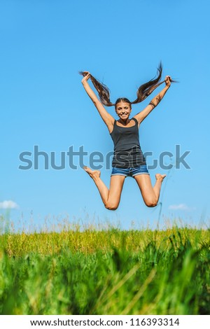 Portrait of young beautiful woman jumps high into sky, on green background summer nature. - stock photo