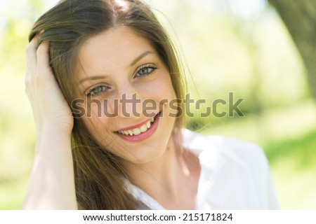 Portrait of young beautiful woman looking at camera on background
