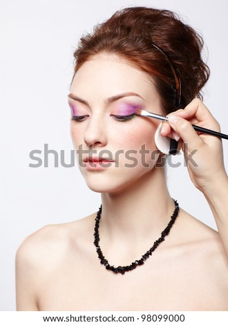portrait of young beautiful woman maked up by makeup artist's hand putting on purple eyeshadow - stock photo