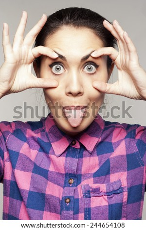 Portrait of young beautiful woman makes a gesture like an owl - stock photo