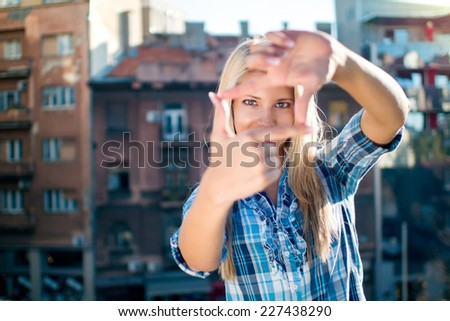 Portrait of young beautiful woman making frame with her hands. - stock photo