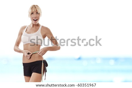 Portrait of young beautiful woman measuring her waist - stock photo