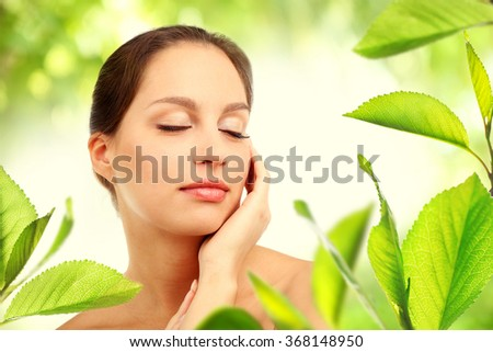 Portrait of young beautiful woman, on green nature background with leaves
