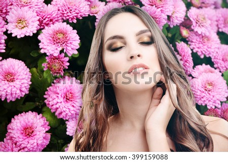 Portrait of young beautiful woman on nature background with flowers