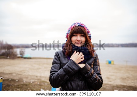 Portrait of young beautiful woman outdoor - standing on seaside and holding waving fabric scarf in her arms on wind