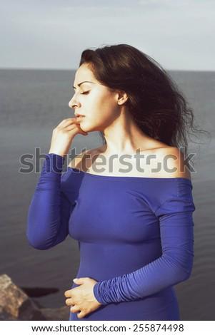 Portrait of young beautiful woman outdoors near sea - stock photo