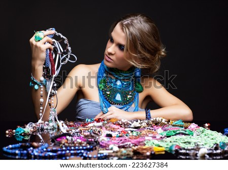 Portrait of young beautiful woman over heap of bijouterie on the table with beads in hands - stock photo