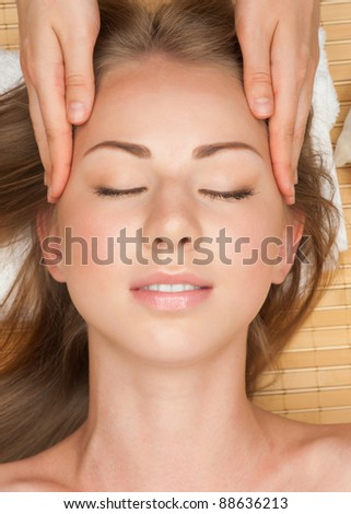 Portrait of young beautiful woman receiving facial massage at spa salon
