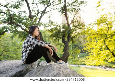 Portrait of young beautiful woman relaxing in Central Park. New York City. Filtered image.