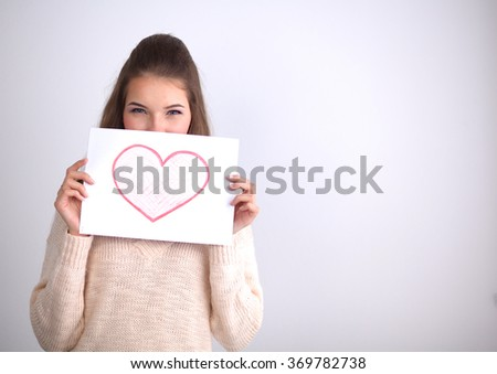 Portrait of young beautiful woman showing gift card. Valentines Day - stock photo