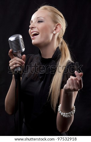 portrait of young beautiful woman singing with retro microphone - stock photo