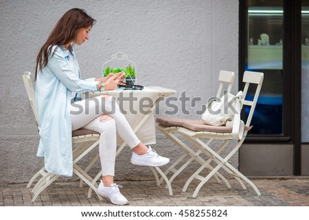 Portrait of young beautiful woman sitting in a cafe outdoor drinking coffee. Happy tourist at openair restaraunt - stock photo