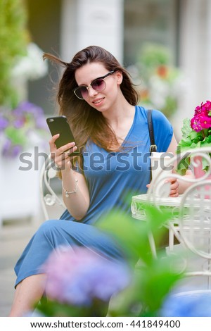 Portrait of young beautiful woman sitting in outdoor cafe drinking coffee and using smartphone. - stock photo