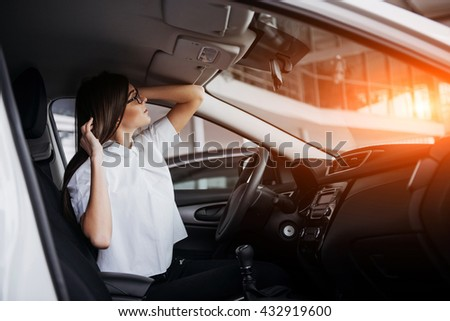 portrait of young beautiful woman sitting in the car - stock photo