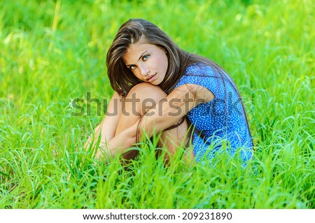 Portrait of young beautiful woman sitting on grass, on green background summer nature.