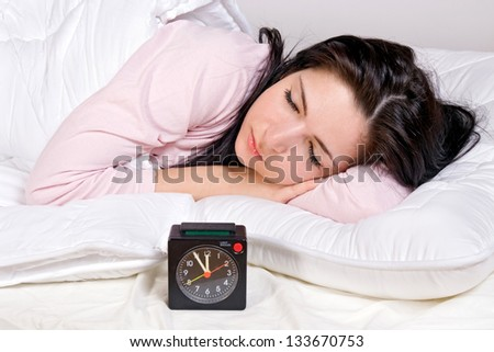 Portrait of young beautiful woman sleeping in bed with alarm clock.