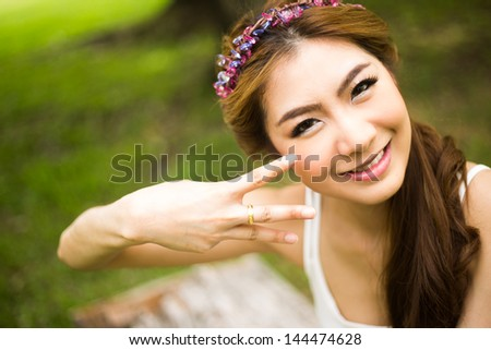 Portrait of young beautiful woman smiling and showing  the ring in the park