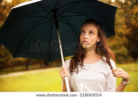 Portrait of young beautiful woman walking in rainy autumn park with umbrella. - stock photo