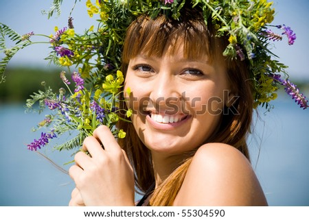 Portrait of Young beautiful woman wearing a wreath of wild flowers - stock photo