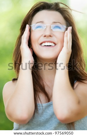 Portrait of young beautiful woman wearing glasses at summer green park - stock photo