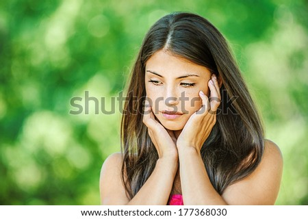 Portrait of young beautiful woman, who looks sadly down, on green background summer nature. - stock photo