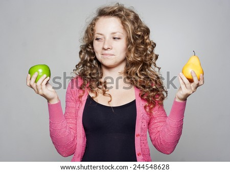 Portrait of young beautiful woman with an apple and pear - stock photo
