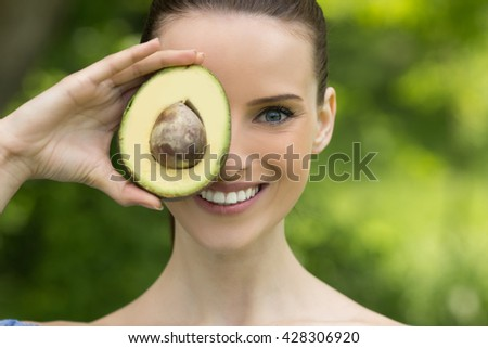 Portrait of young beautiful woman with bare shoulders and avocado - stock photo