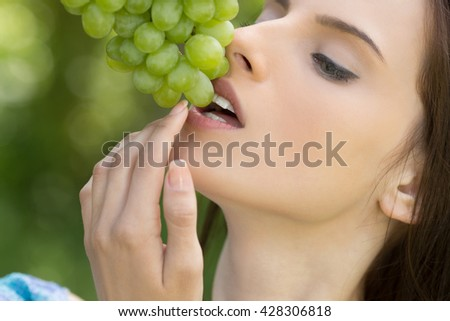 Portrait of young beautiful woman with bare shoulders and grapes