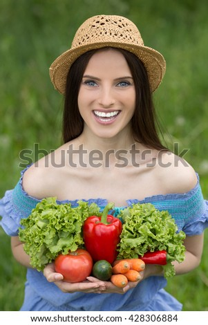 Portrait of young beautiful woman with bare shoulders and red pepper, cucumber, tomato, carrot, parsley