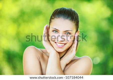 Portrait of young beautiful woman with bare shoulders crossed her arms and smilling, on green background summer nature.