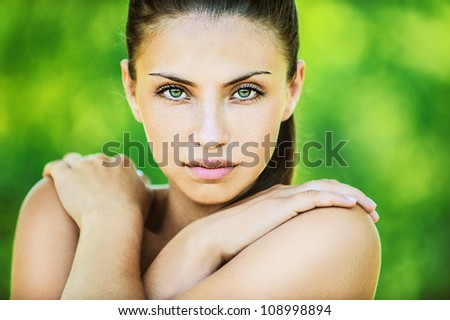 Portrait of young beautiful woman with bare shoulders crossed her arms, on green background summer nature. - stock photo
