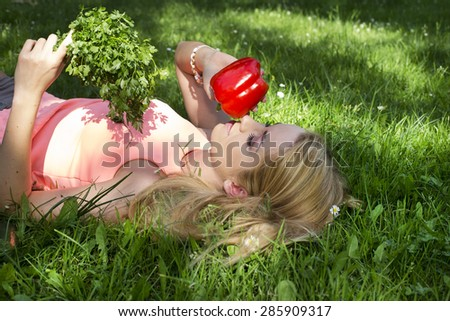 Portrait of young beautiful woman with bare shoulders holding a vegetable on green background summer nature.