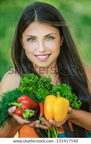 Portrait of young beautiful woman with bare shoulders holding a vegetable - parsley, pepper, eggplant, on green background summer nature.