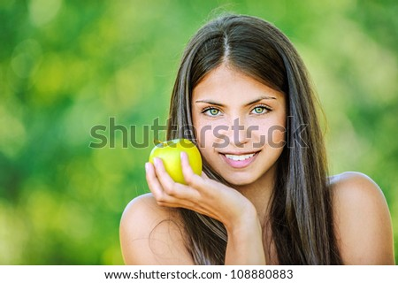 Portrait of young beautiful woman with bare shoulders holding an apple and smiling, on green background summer nature.