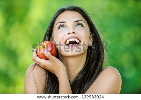 Portrait of young beautiful woman with bare shoulders holding an red apple and smiling, on green background summer nature. - stock photo