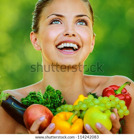 Portrait of young beautiful woman with bare shoulders holding fruit and vegetables - peppers, apples, eggplant, parsley, grapes, on green background summer nature.