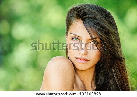 Portrait of young beautiful woman with bare shoulders , on green background summer nature. - stock photo