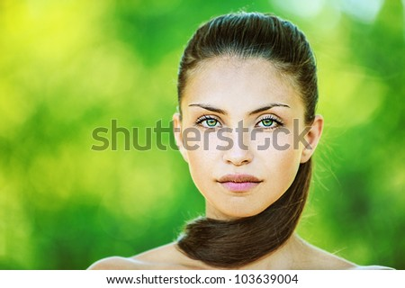 Portrait of young beautiful woman with bare shoulders, on green background summer nature. - stock photo