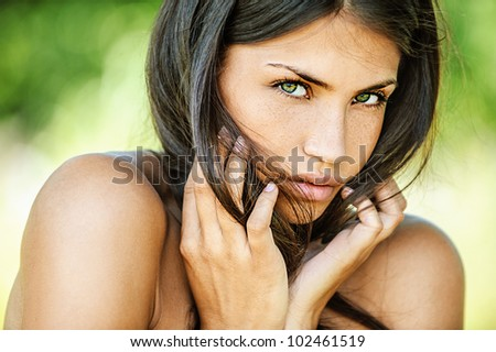 Portrait of young beautiful woman with bare shoulders sad looking at camera, on green background summer nature.