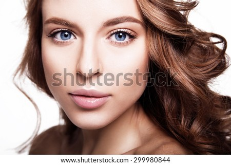Portrait of young beautiful woman with blue eyes and nude makeup, curly hair. White background. - stock photo