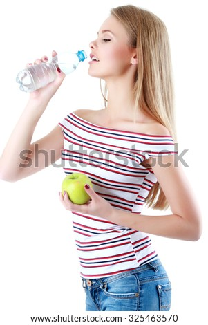 Portrait of young beautiful woman with bottle of mineral water and apple