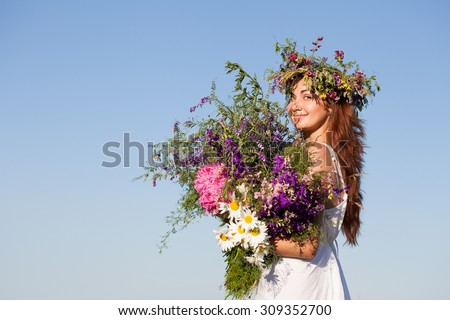 Portrait of Young beautiful Woman with Bouquet, wearing a Wreath of wild flowers. Blue sky - stock photo
